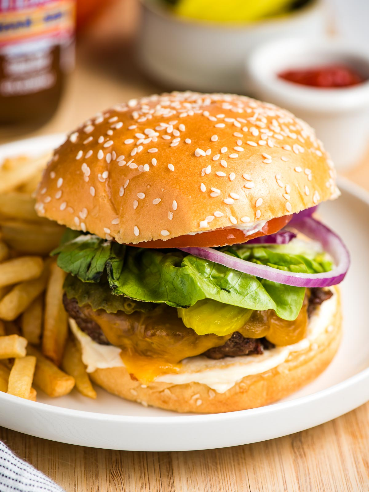 An air fryer hamburger on a plate with fries.