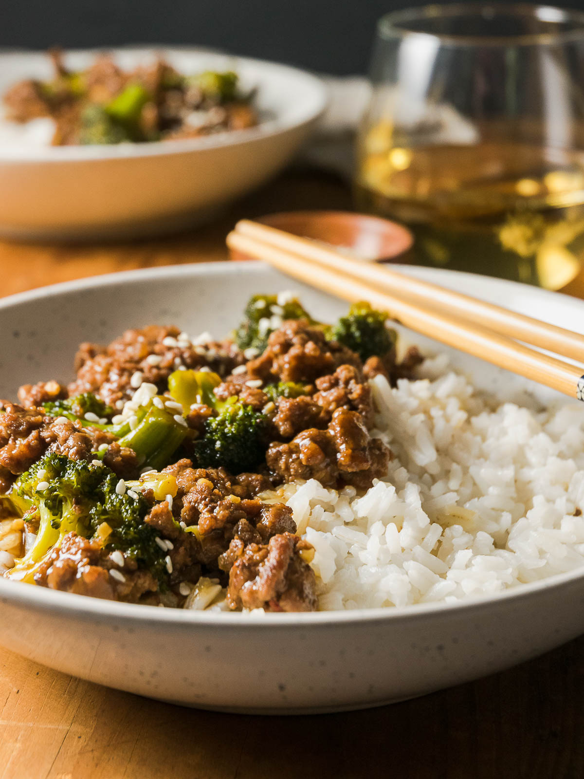 Closeup on a bowl of Ground Beef and Broccoli with rice served on a table with a drink and chopsticks.