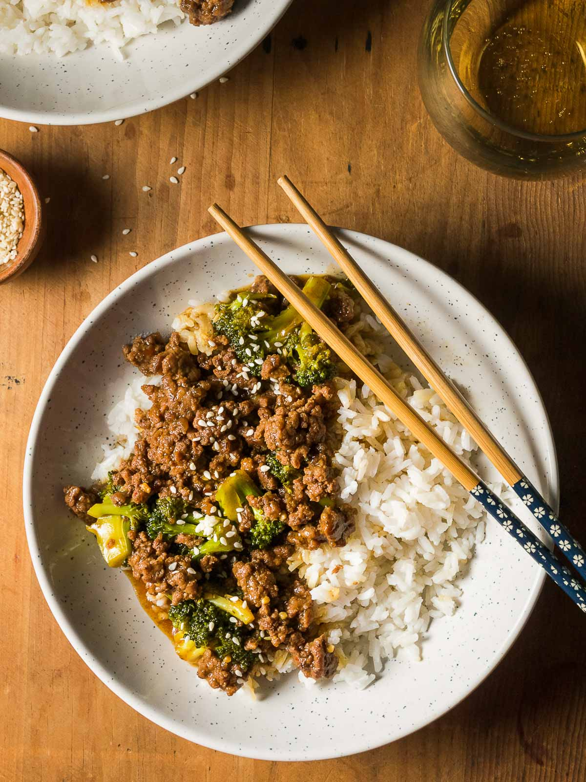 Overhead of a bowl of Ground Beef and Broccoli stir fry and rice with chopsticks.
