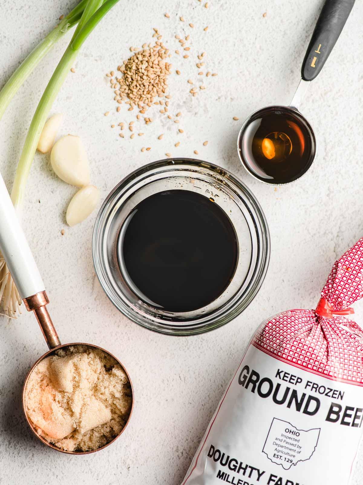 Ingredients in Korean bulgogi on a white background-brown sugar, green onions, sesame seeds, sesame oil, garlic, and ground beef.
