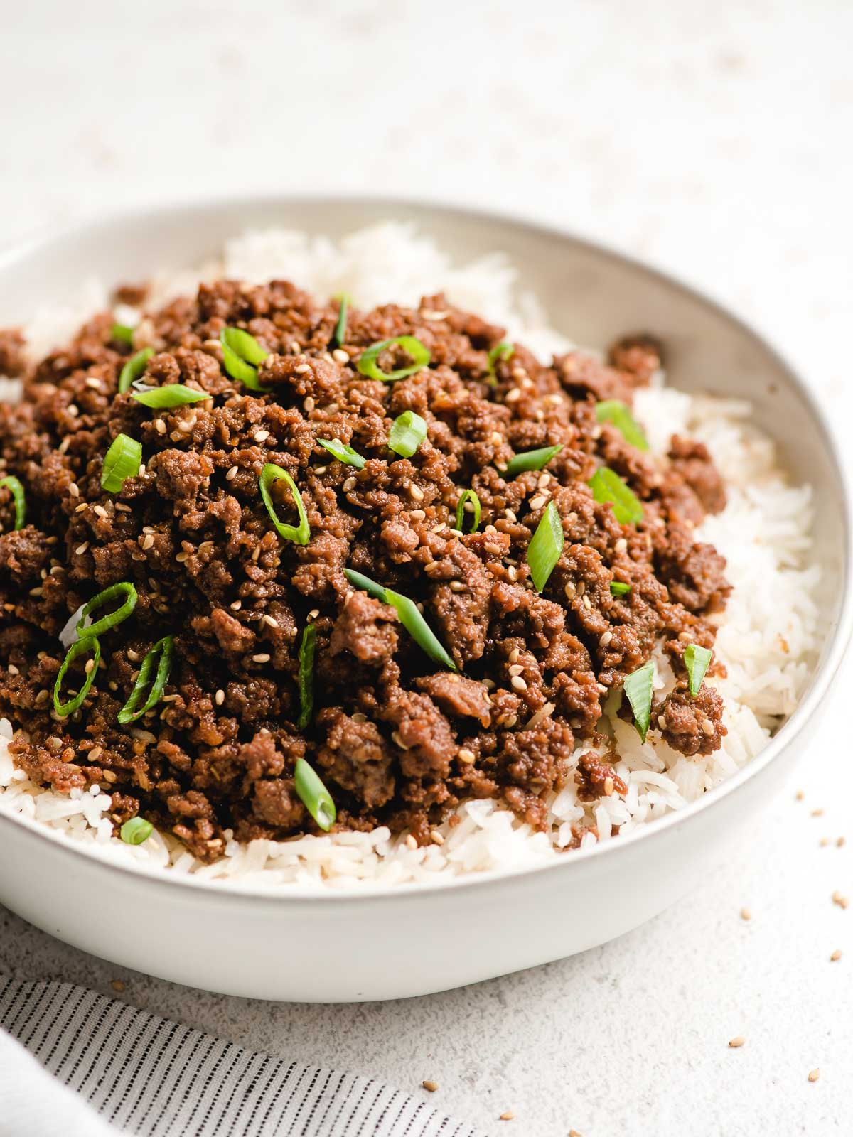 Ground beef bulgogi topped with sliced green onions in a white bowl.