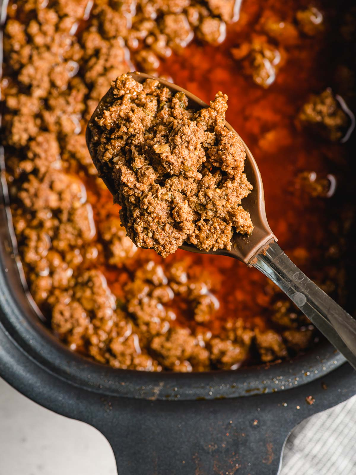 Crock Pot Taco Meat being scooped with a spoon.