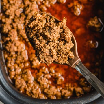 A spoon scoops crock pot taco meat our of a slow cooker.