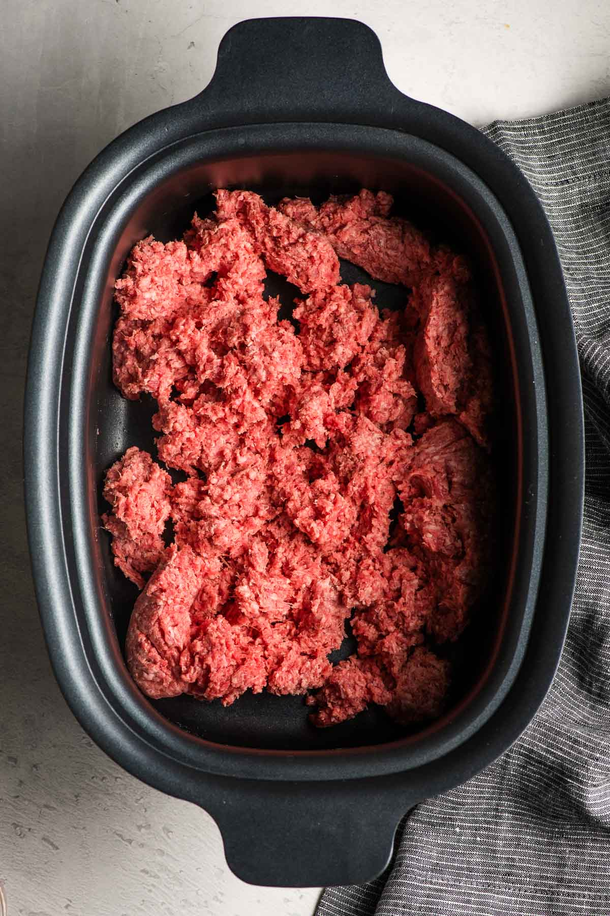 Raw Ground Beef in a slow cooker.
