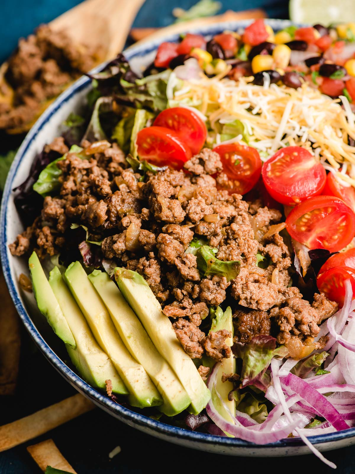 A bowl of ground beef taco salad is served with a wooden spoon.