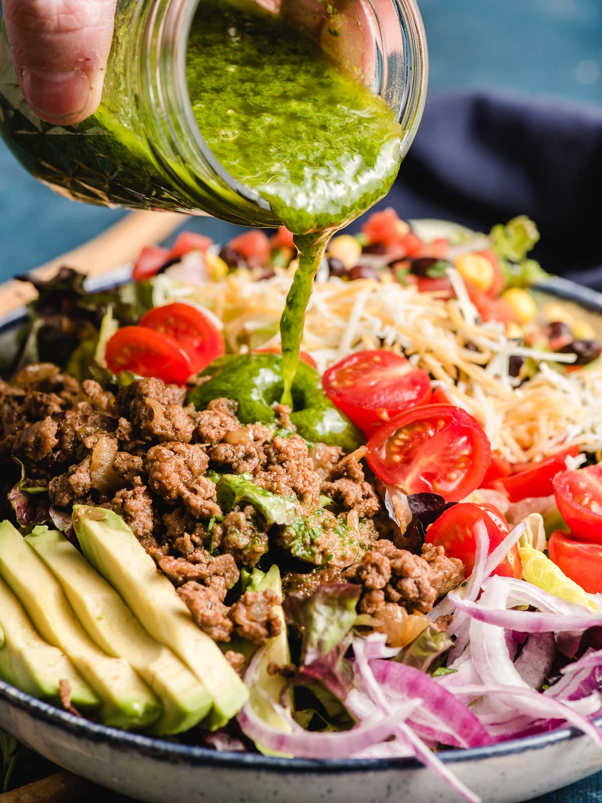 Cilantro Lime Vinaigrette dressing being poured on a bowl of Ground Beef Taco Salad.
