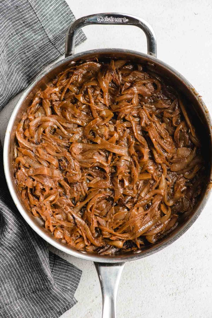 A deep stainless steel skillet filled with caramelized onions.