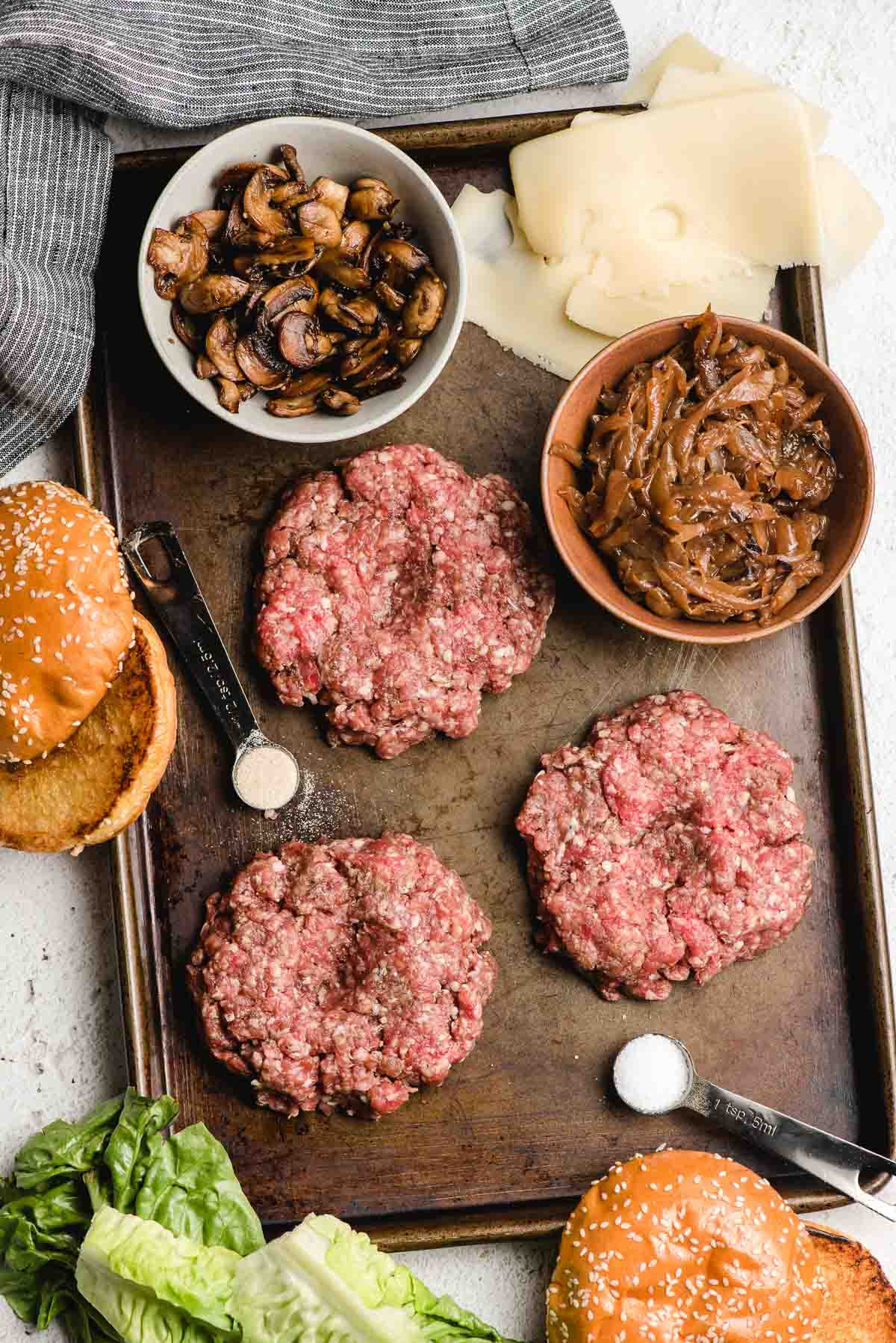 Ingredients for mushroom swiss burgers on a sheet pan. Includes the raw burger patties, plus bowls of sauteed mushrooms and carmalized onions, cheese slices, and buns.